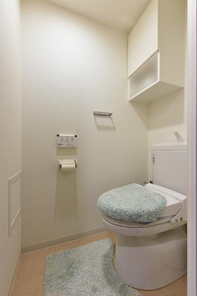 温水洗浄機能付暖房便座採用のトイレ。吊戸棚にはトイレットペーパーなどの消耗品が収納できます。
