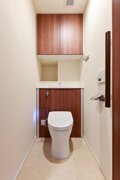 キャビネット付トイレには手洗い器を設置。温風乾燥やオート開閉、オート便座洗浄など高機能な仕様です。