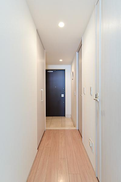 廊下/居住スペースに配慮した廊下部分。家事道具などを収納できる物入と玄関には下足入れがございます。