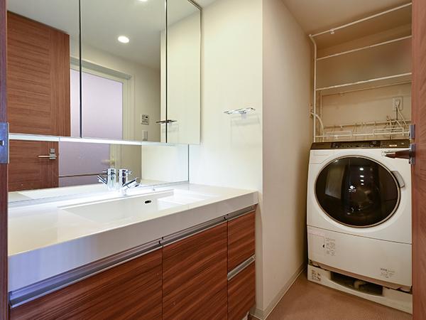 リネン庫を備えたパウダールーム。落ち着いた色調で心地よい空間です。