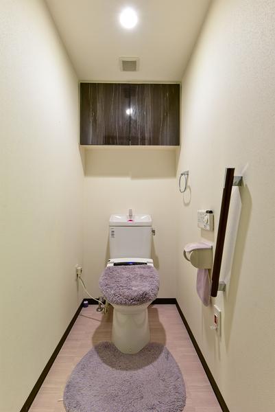温水洗浄機能付きトイレ。吊戸棚がございますので用具等がスッキリ片付きます。