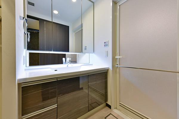 ワイドミラーの三面鏡を備えた洗面化粧台。スキンケア用品やヘアケア用品などを整理できる三面鏡裏収納棚。