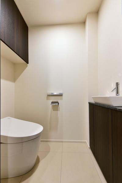 お掃除の手間が軽減されるタンクレストイレ。独立した手洗い場や吊戸棚を設けた機能性良好な空間。